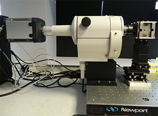 Set-up at Levy's lab showing the Nikon AZ-100 lying horizontally with the Neo attached on one side and the custom designed NdFeB magnet on the other side.